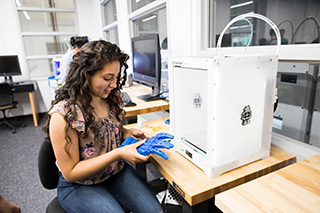 Photo of student at 3D printer in Baxter Innovation Lab