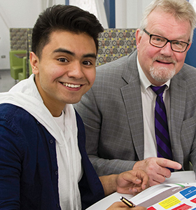 Student Trustee Hansel Lopez and Board Chair Richard A. Anderson chat in Café Willow