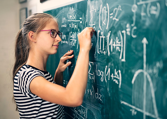 Young female student solving math problem on blackboard