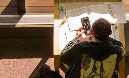 Student working at desk with book and calculator
