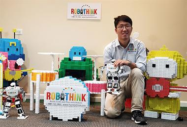 Robothink CEO Danny Park with robots made with building blocks